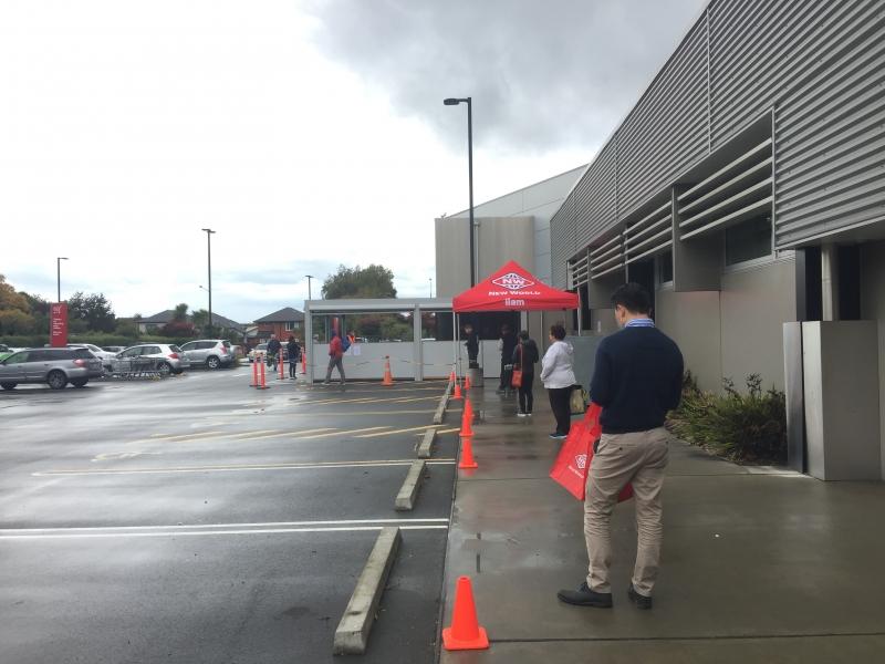 スーパーマーケットの前で並んで待つ人々